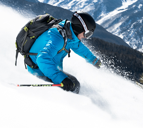 man downhill skiing in blue obermeyer jacket